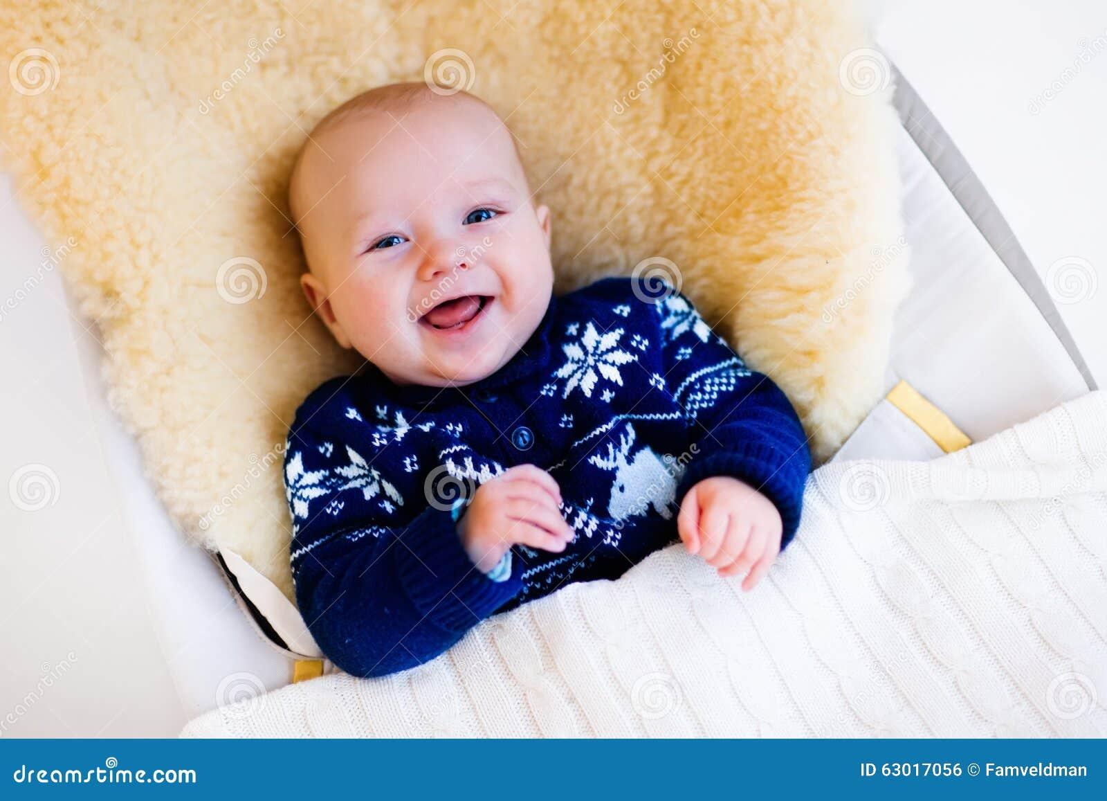 Little Baby In Nordic Sweater On Sheepskin Stock Photo