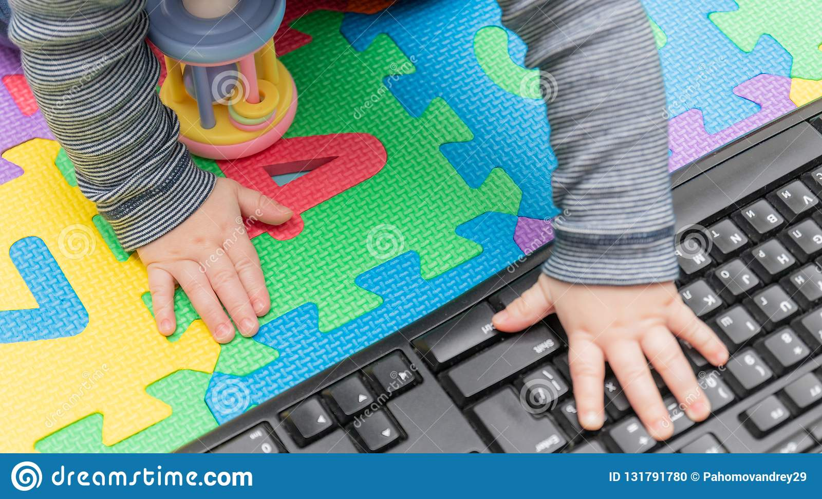 Little baby`s hands, on a computer mouse and keyboard - child development, getting familiar with technology since their early age