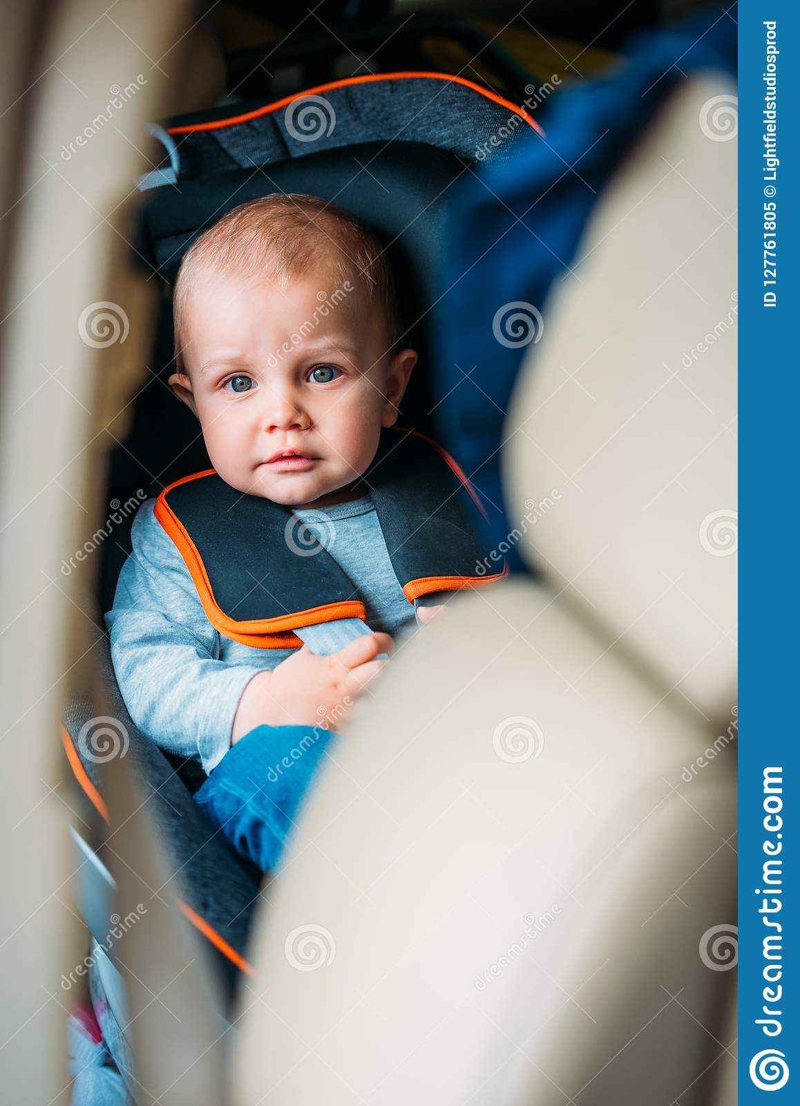 little baby sitting in child safety seat in car and looking