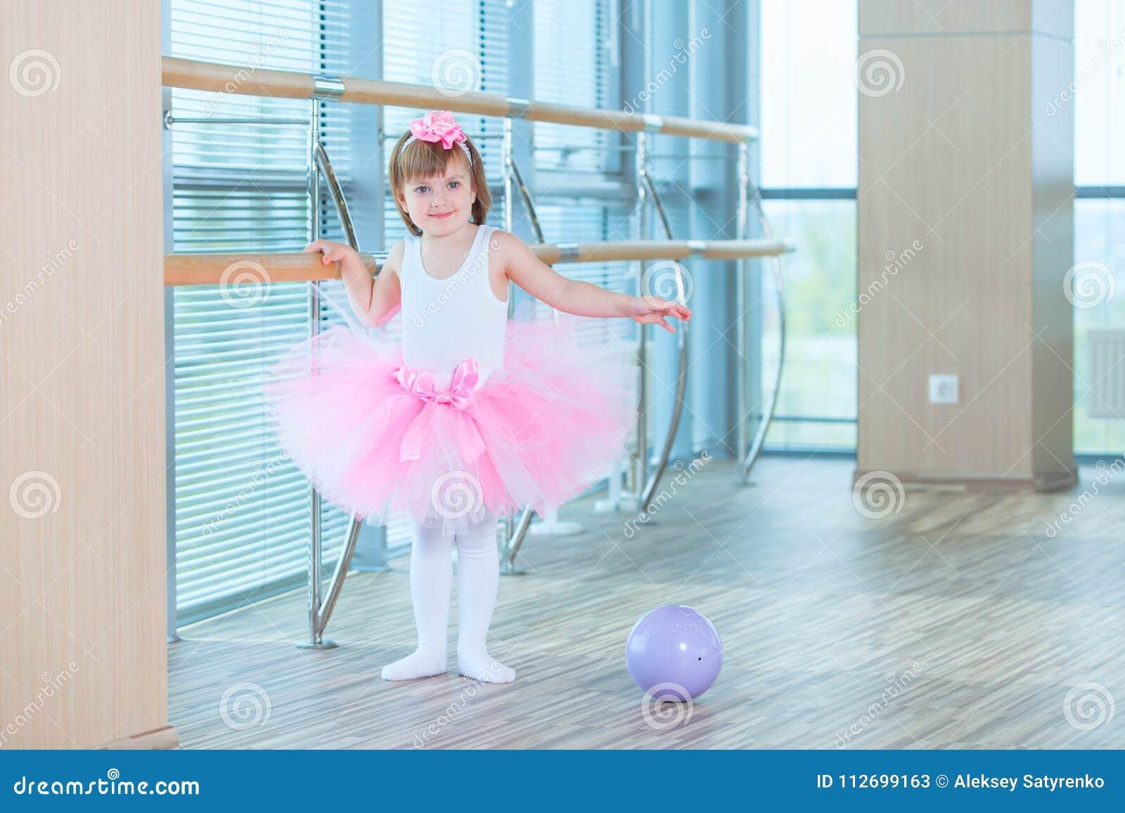 Little ballerina girl in a pink tutu. Adorable child dancing classical ballet in a white studio. Children dance. Kids