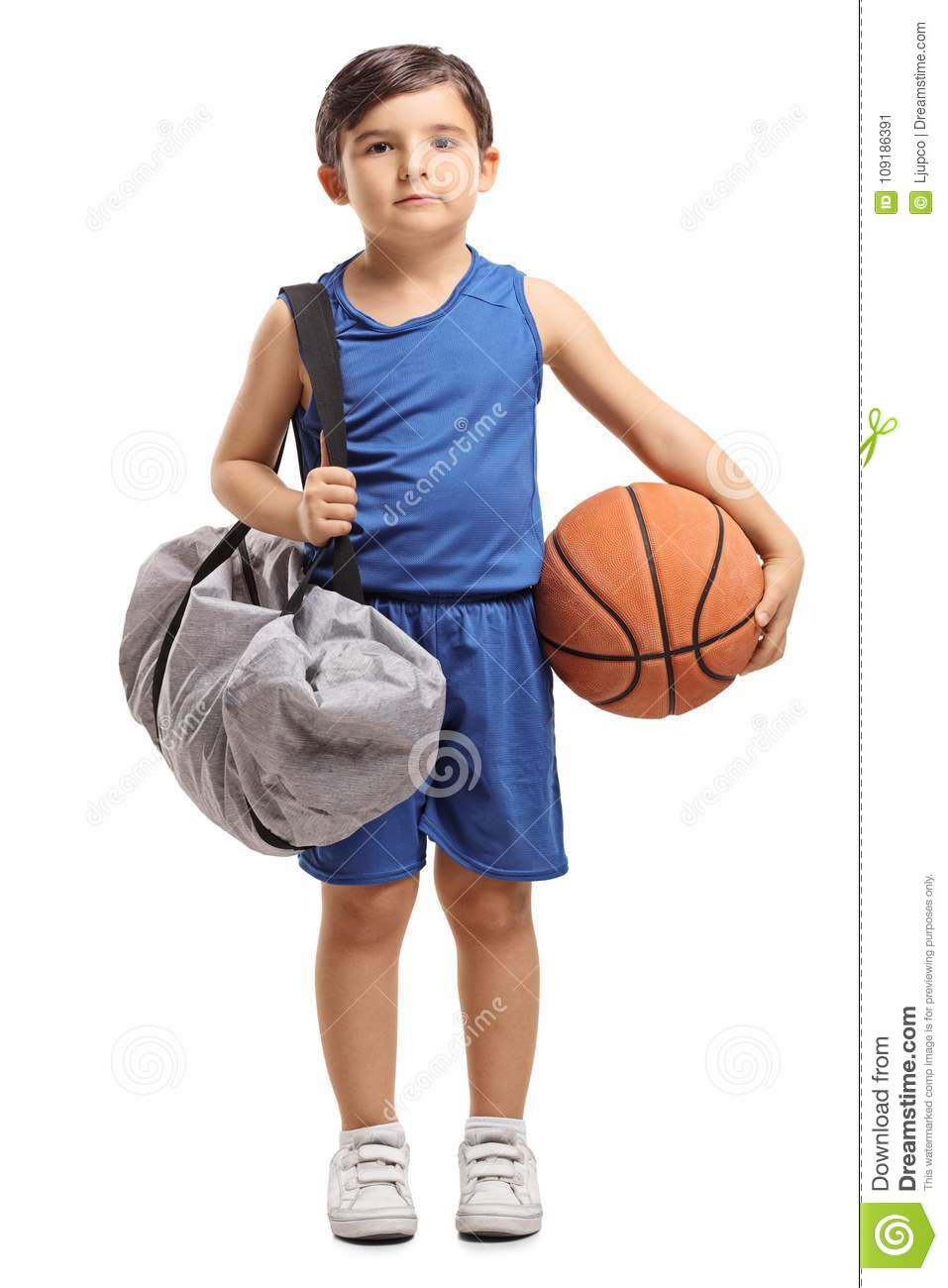 3a283e960cd Full length portrait of a little basketball player holding a sports bag and  a basketball isolated on white background