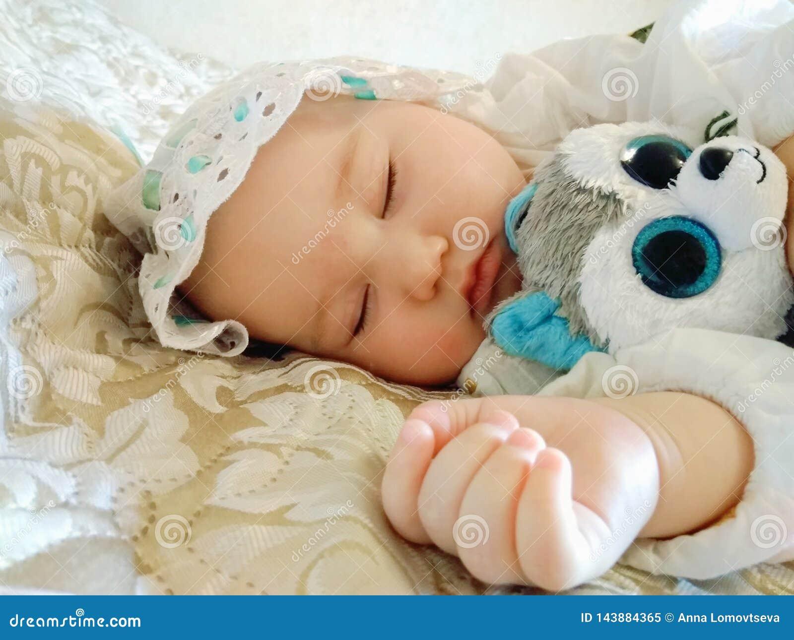 Little beautiful baby sleeps on a beige bed