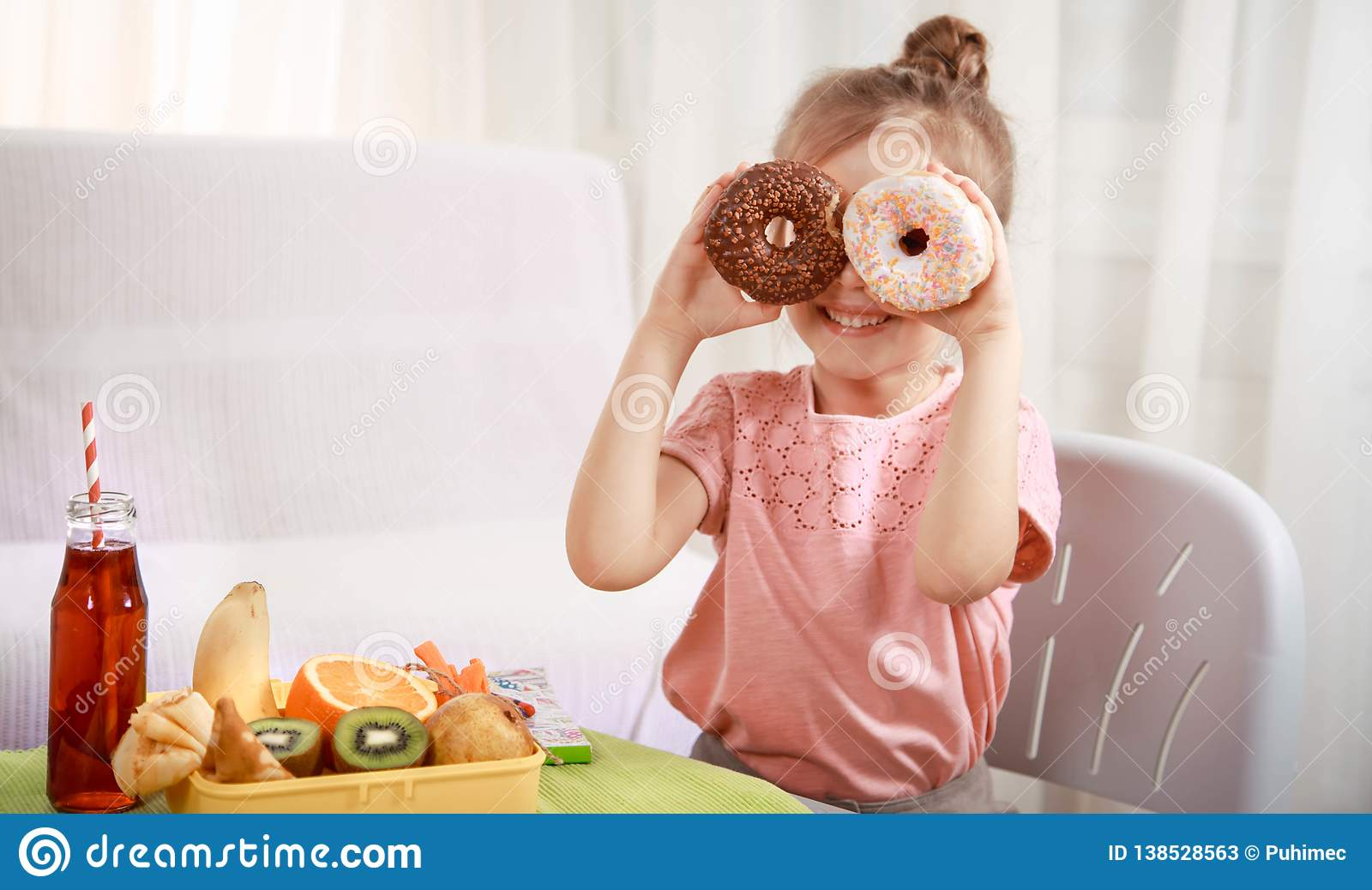 Little beautiful cheerful girl eating a donut