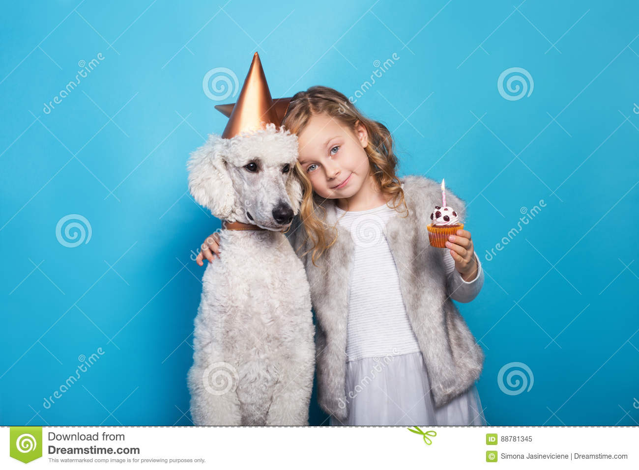 Little beautiful girl with dog celebrate birthday. Friendship. Love. Cake with candle. Studio portrait over blue background
