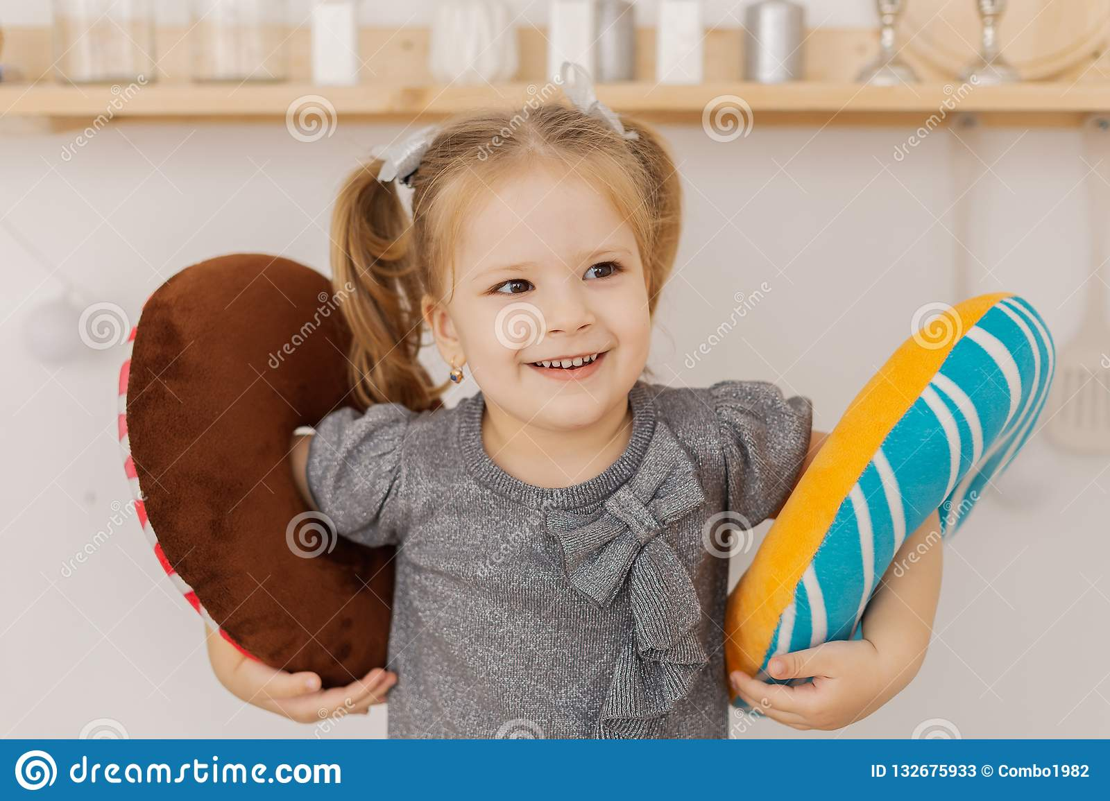 Little beautiful girl playing in the kitchen with colorful toys.