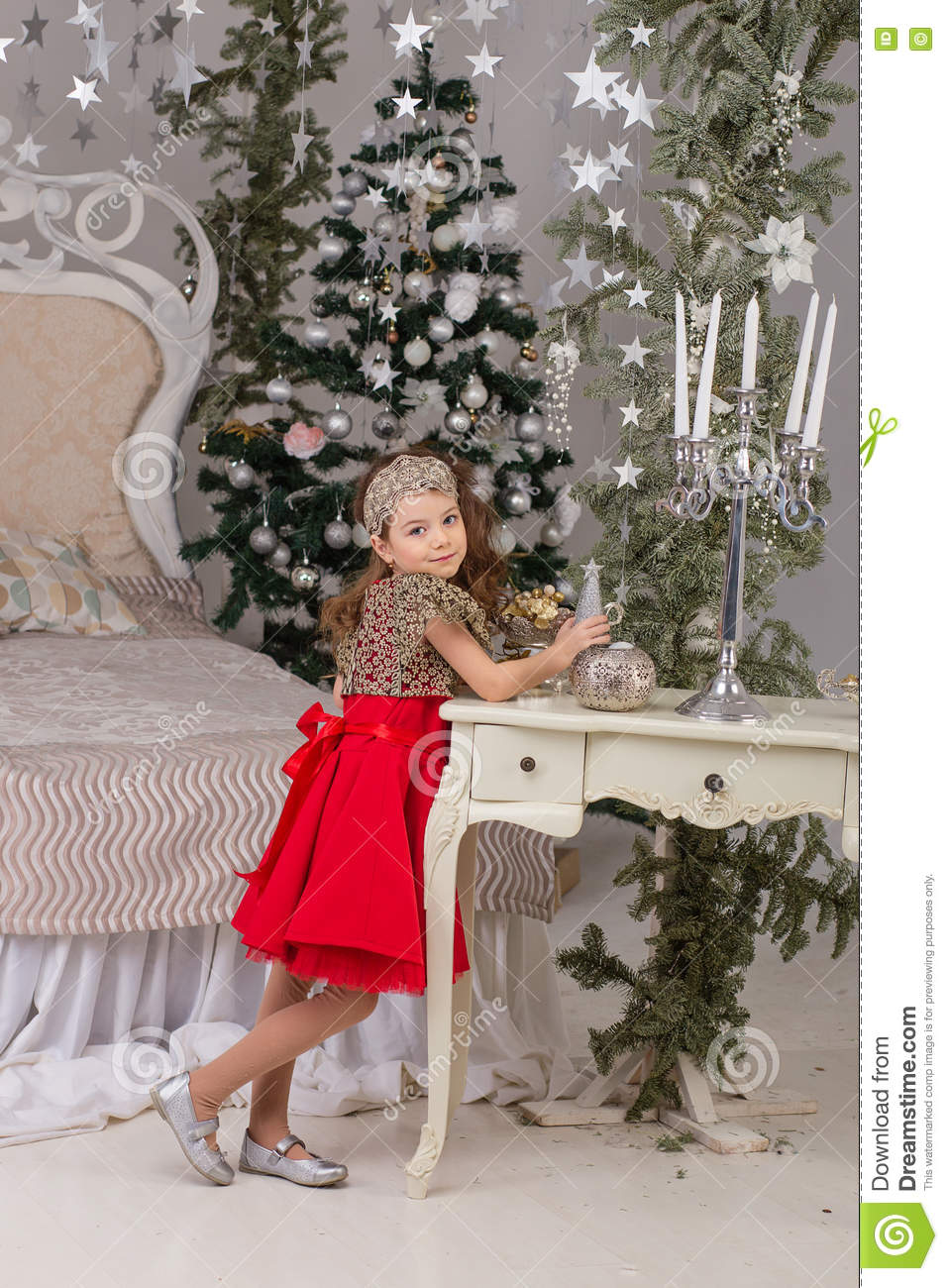 f0abdc75da3de Little beautiful girl in a red evening dress the Christmas tree. Girl in red  in Christmas decorations. Cute child on the bed