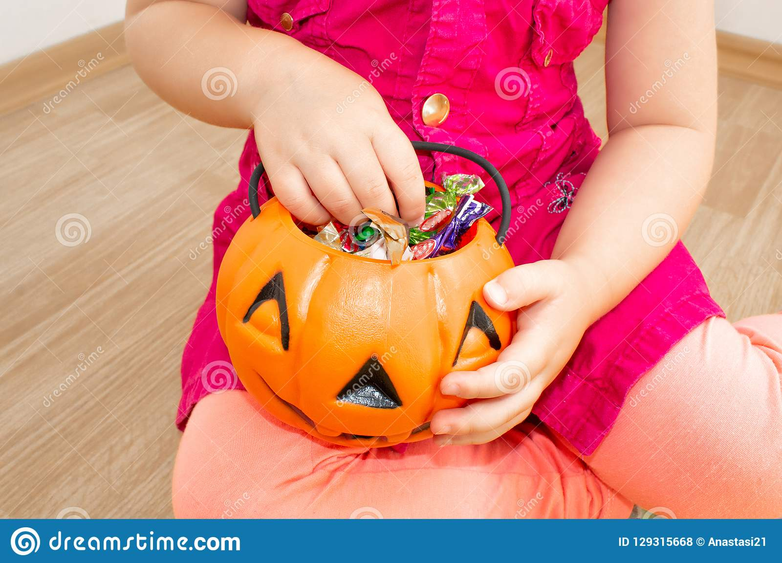 Little beautiful girl sitting with a pumpkin with candies in her hands, on Halloween.