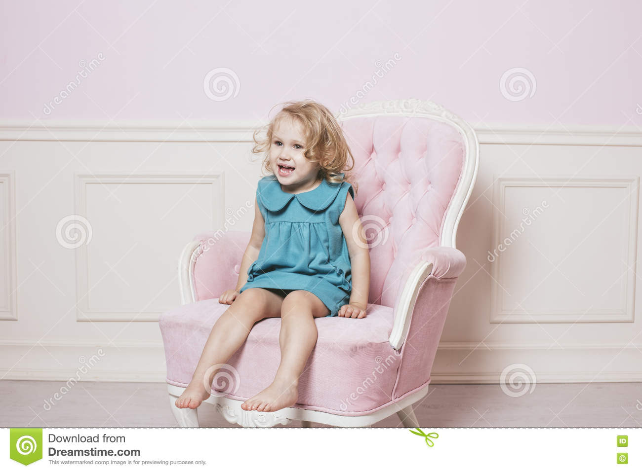 Little beautiful and happy baby girl sitting on a for Toddler sitting chair