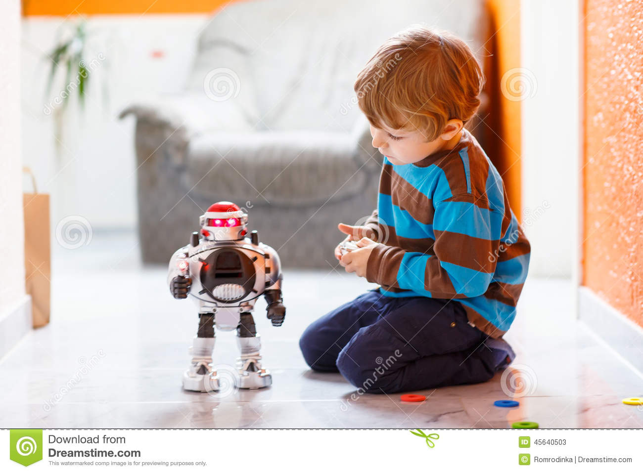 Little Blond Boy Playing With Robot Toy At Home Indoor
