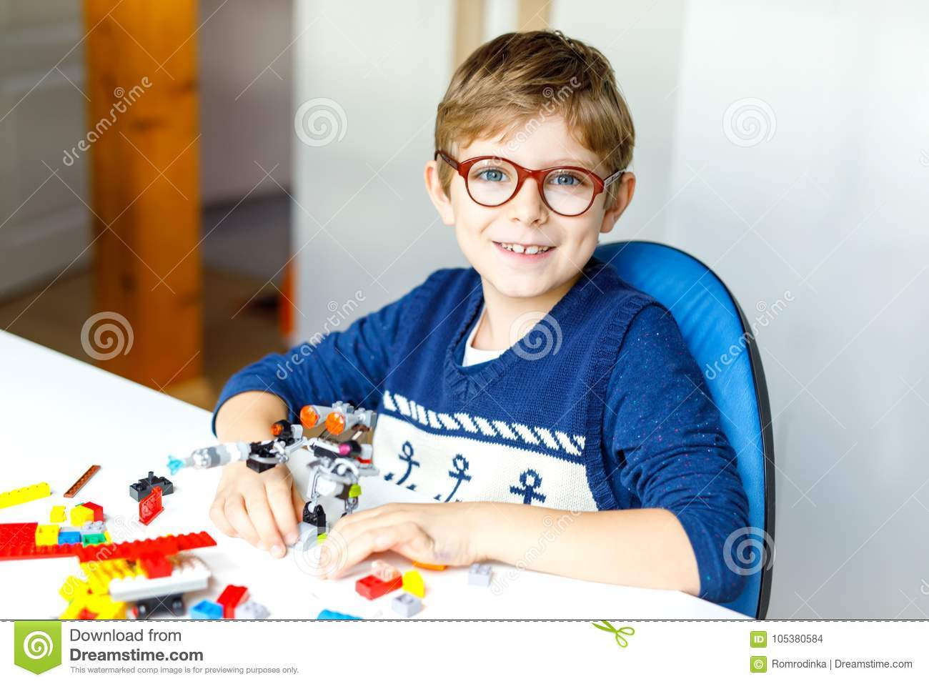 Little blond child with eye glasses playing with lots of colorful plastic blocks.
