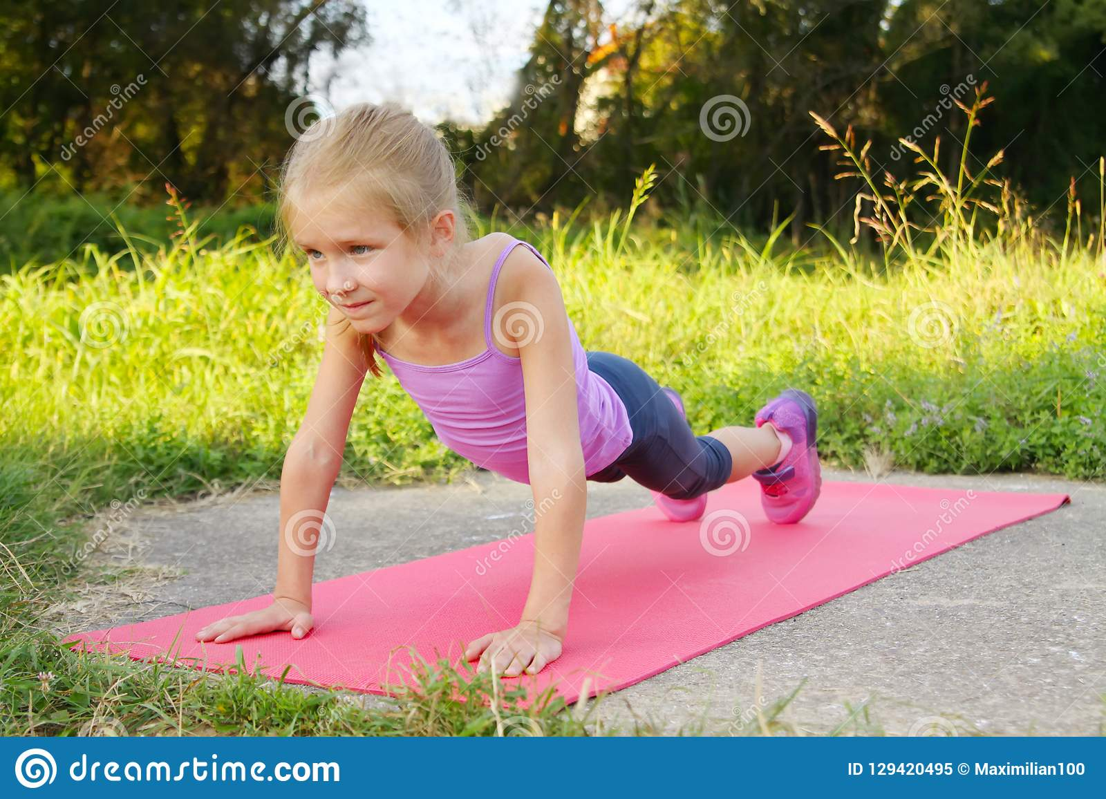 Little blond girl doing fitness exercises plank in the park