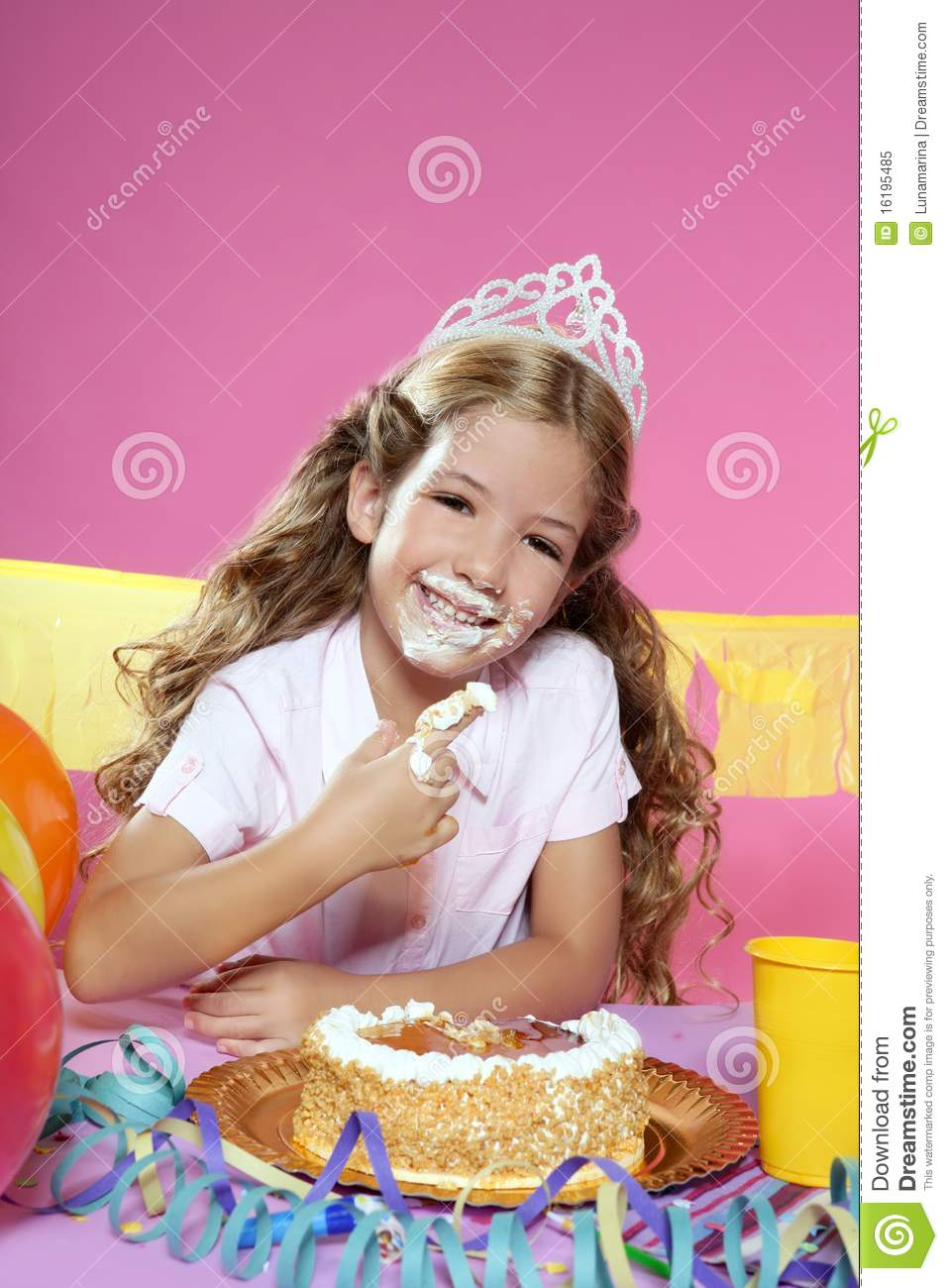 little blond girl eating birthday cake with hands stock