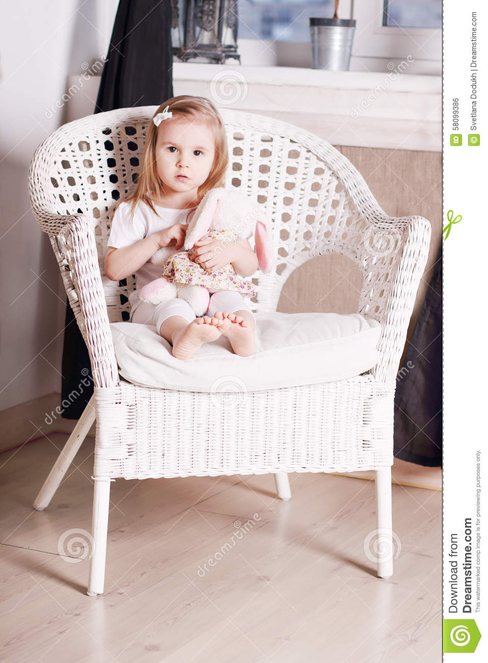 Little Blond Girl With Soft Toy Sits On Large Wicker Chair