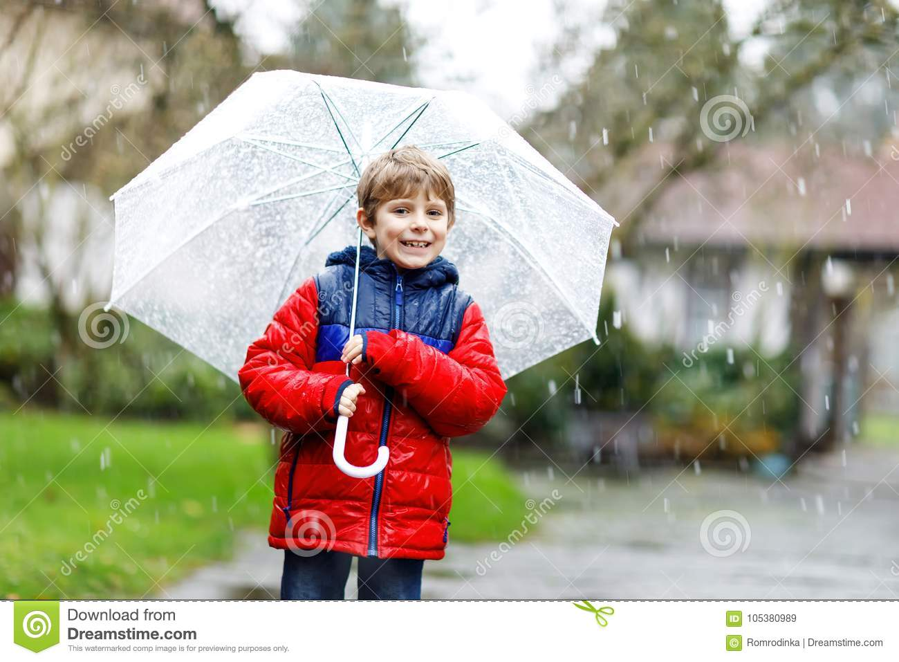 Little blond kid boy on way to school walking during sleet, rain and snow with an umbrella on cold day
