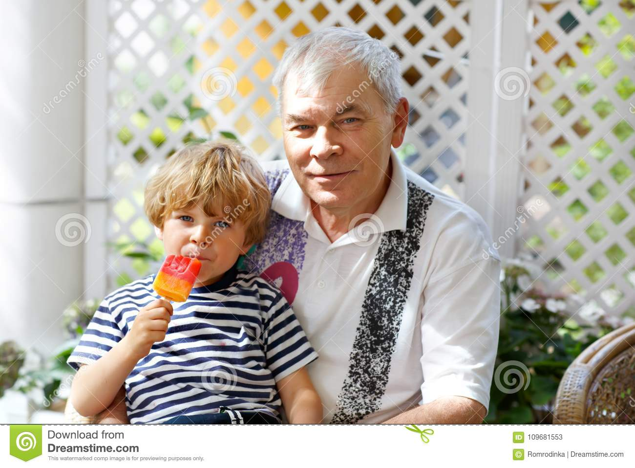 Little blond kid boy and young senior grandfather eating together ice cream in summer