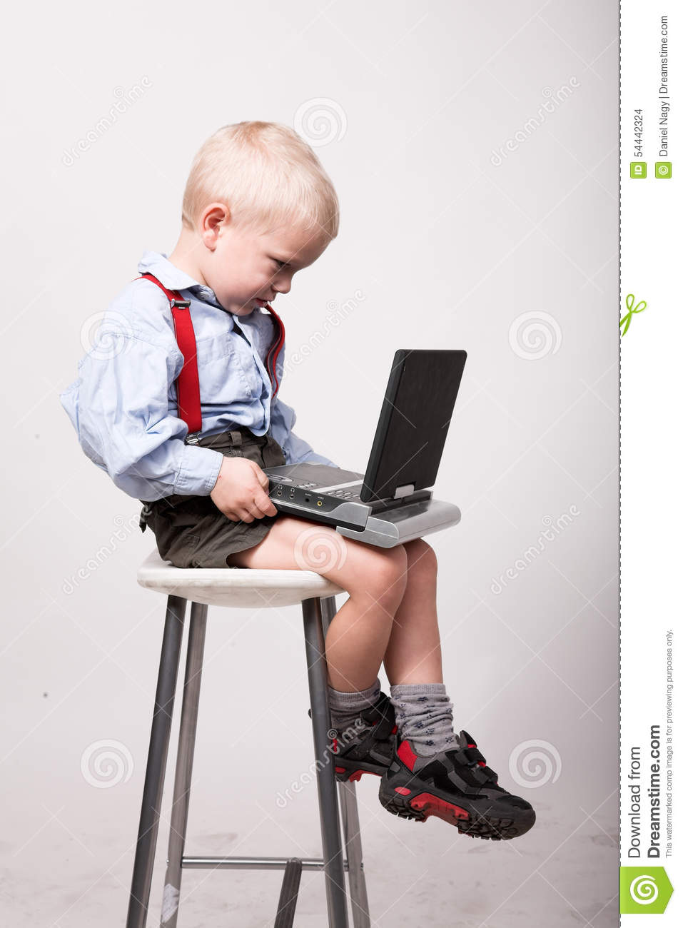 Little blonde boy sits on chair with portable dvd player