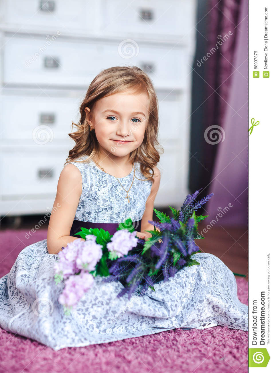 Little blonde girl in a beautiful dress sits on the floor with little blonde girl in a beautiful dress sits on the floor with flowers on her knees izmirmasajfo Image collections