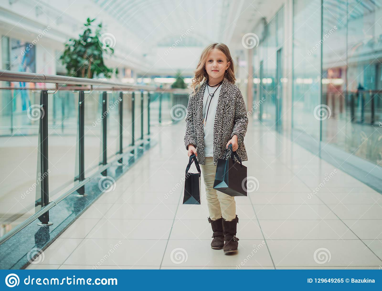 Little blonde girl is shopping at the Mall. Next to the black bags. Black Friday concept. Sale in stores