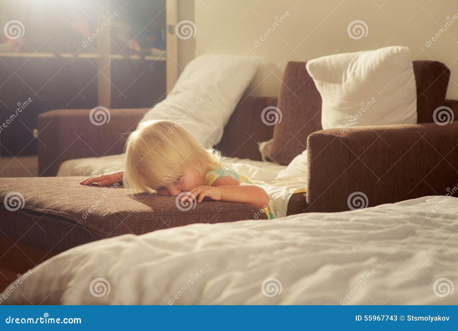 Little Blonde Girl Stands Near Sofa Against White Pillows