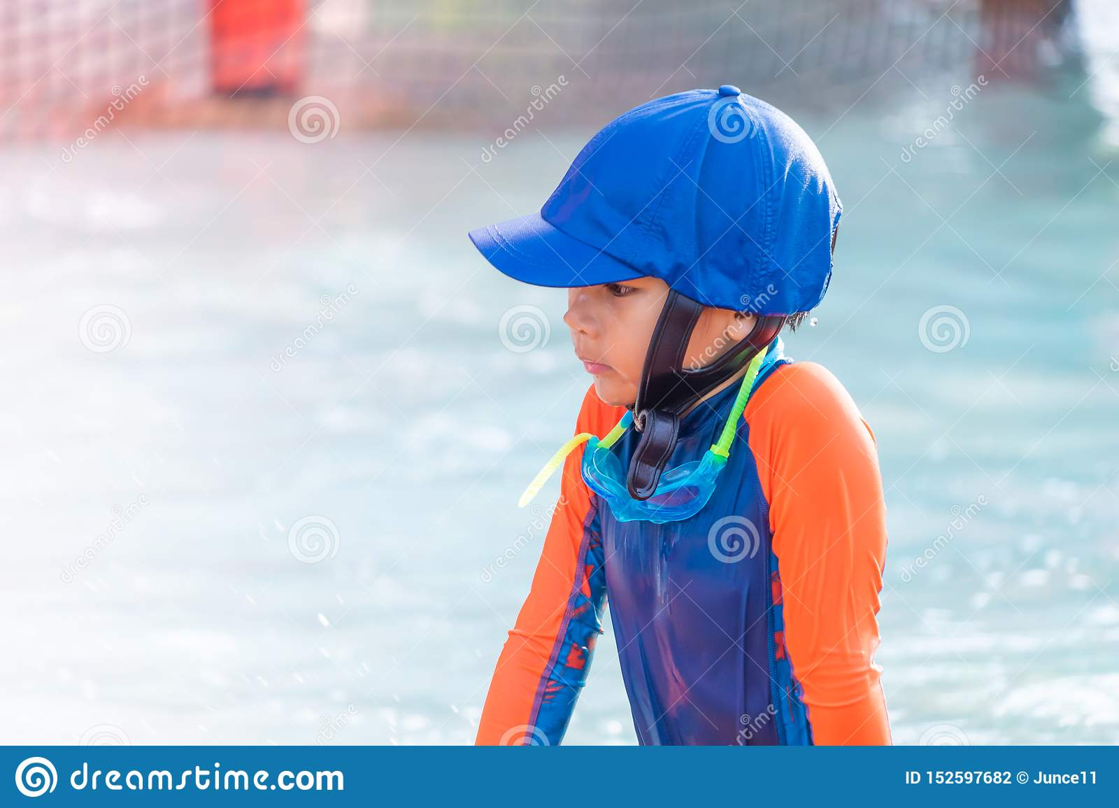 Boy with blue hat and orange suit is playing in swimming pool