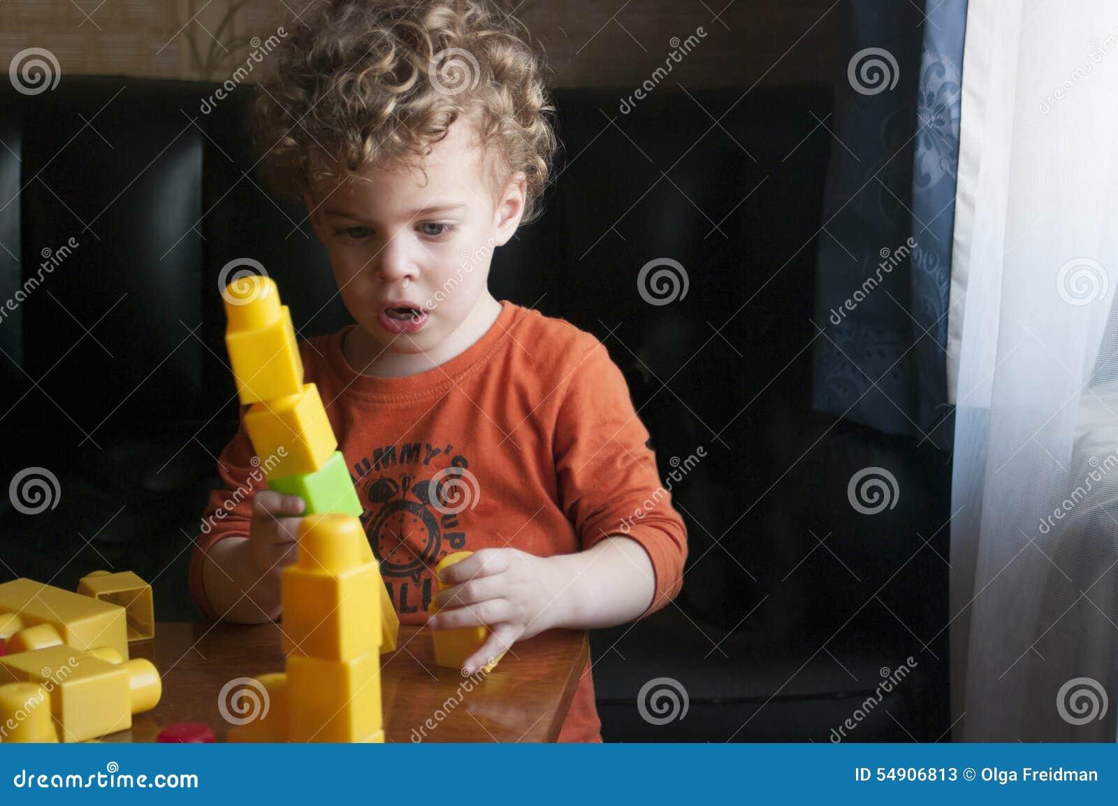 Little boy builds a tower