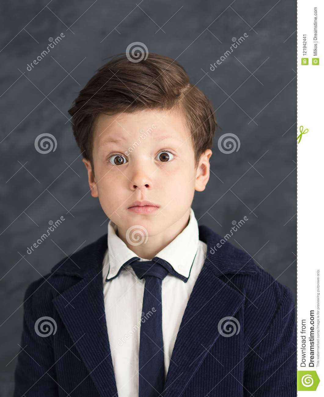 Little boy in business suit with shocked expression