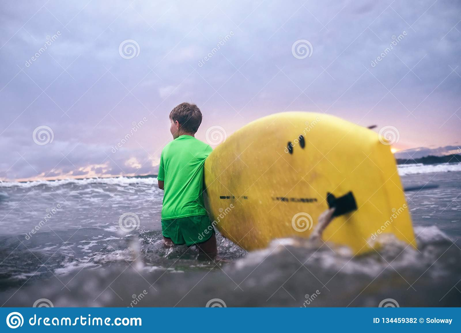 Little boy carries yellow surf board into ocean waves. Surfing First steps concept
