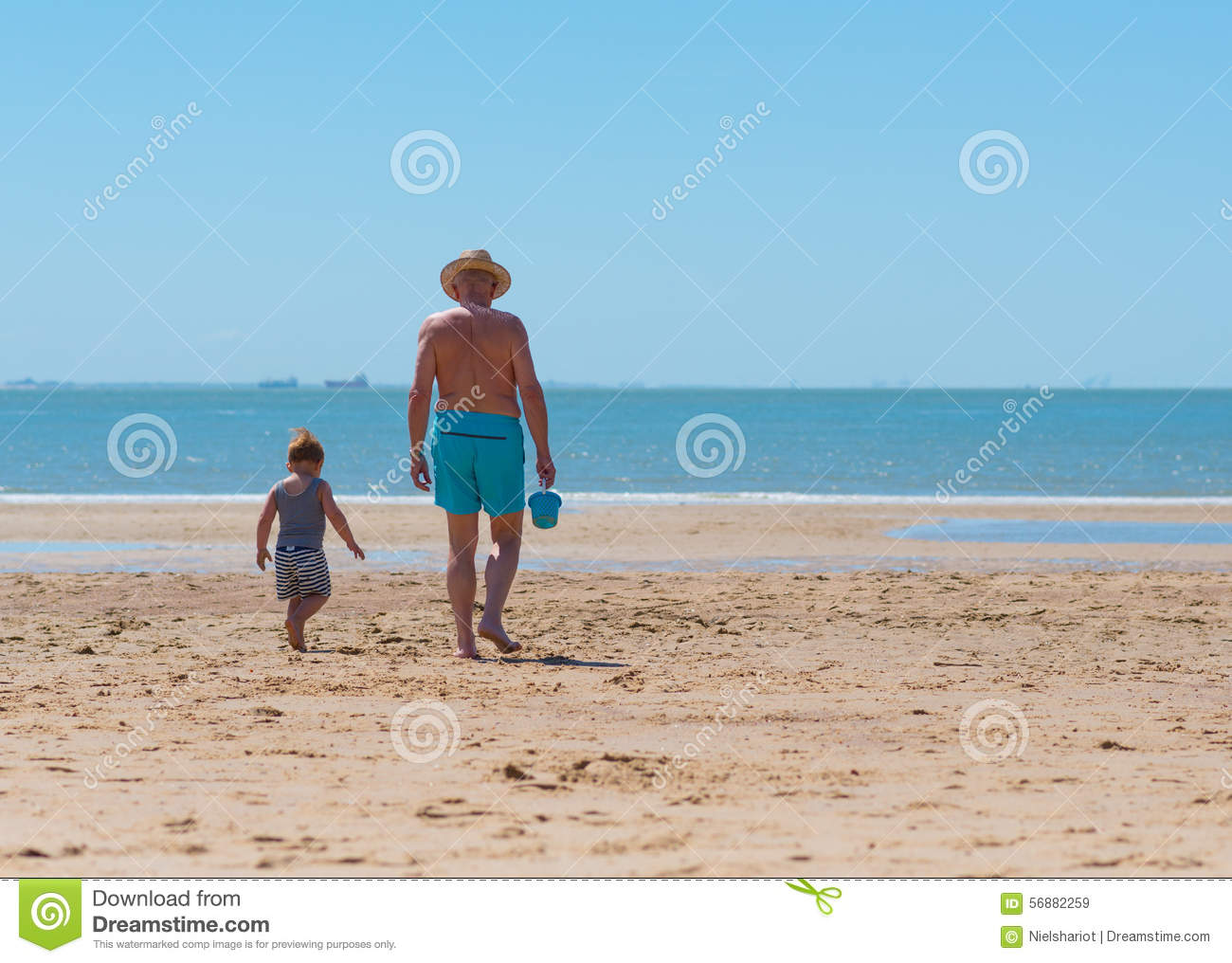 Little boy child with grandfather on the beach