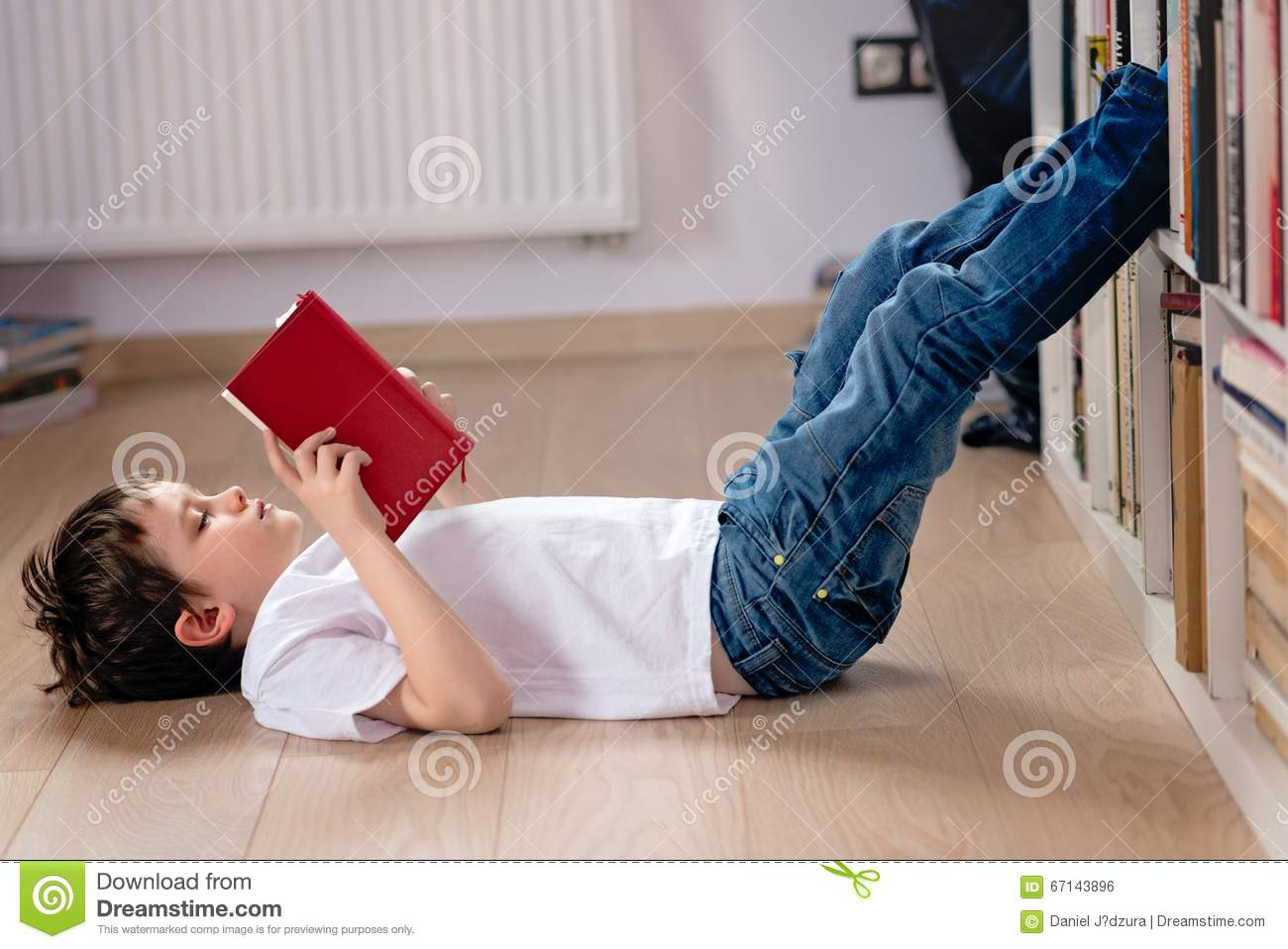 Little boy child reading a book in the library.