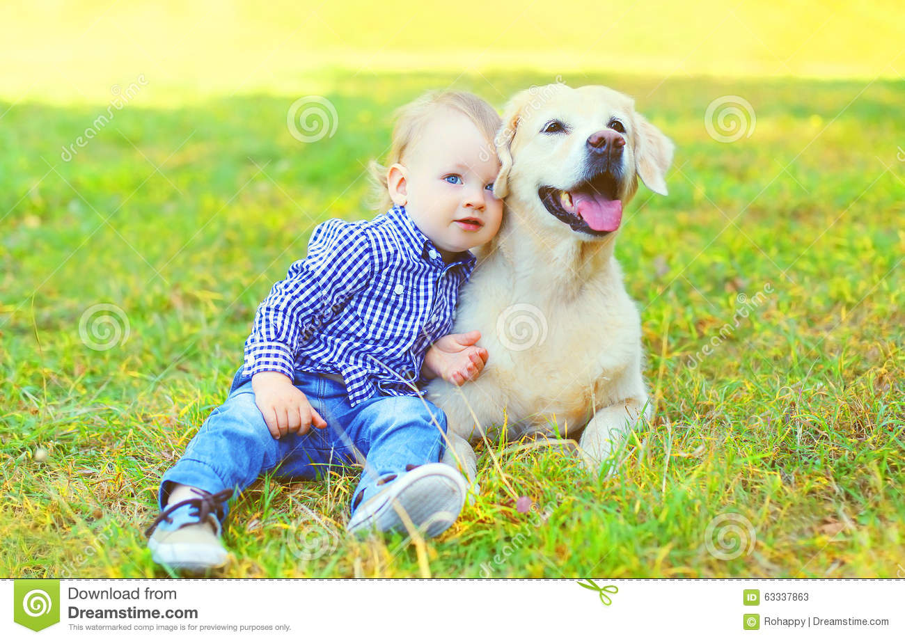 Little boy child sitting with Golden Retriever dog