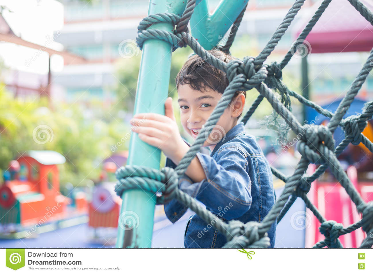 Little boy climbing on the rope at playground outdoor
