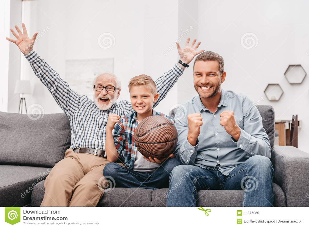 Little boy on couch with grandfather and father, cheering for a basketball game and holding a