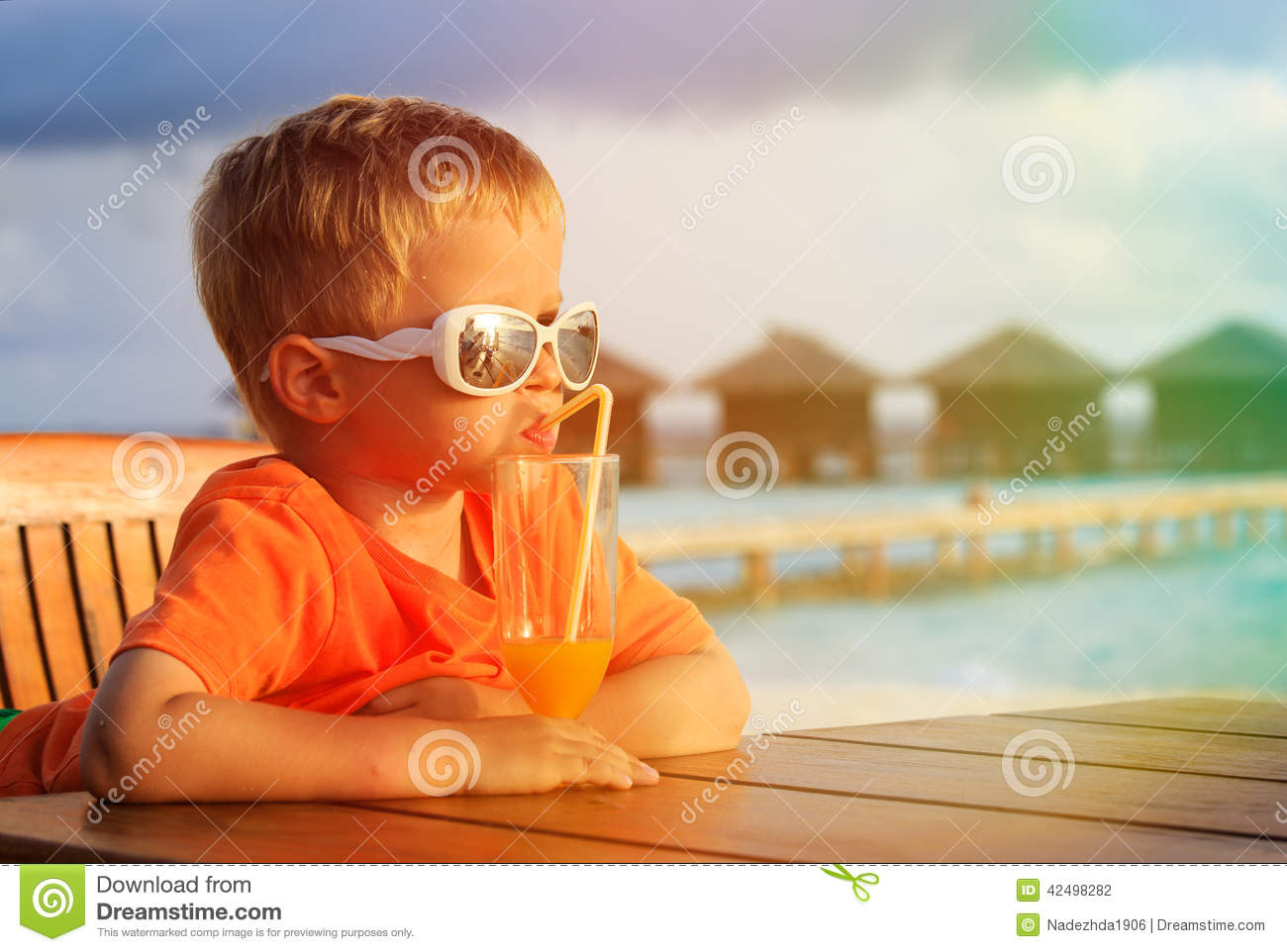 Little boy drinking cocktail on tropical beach