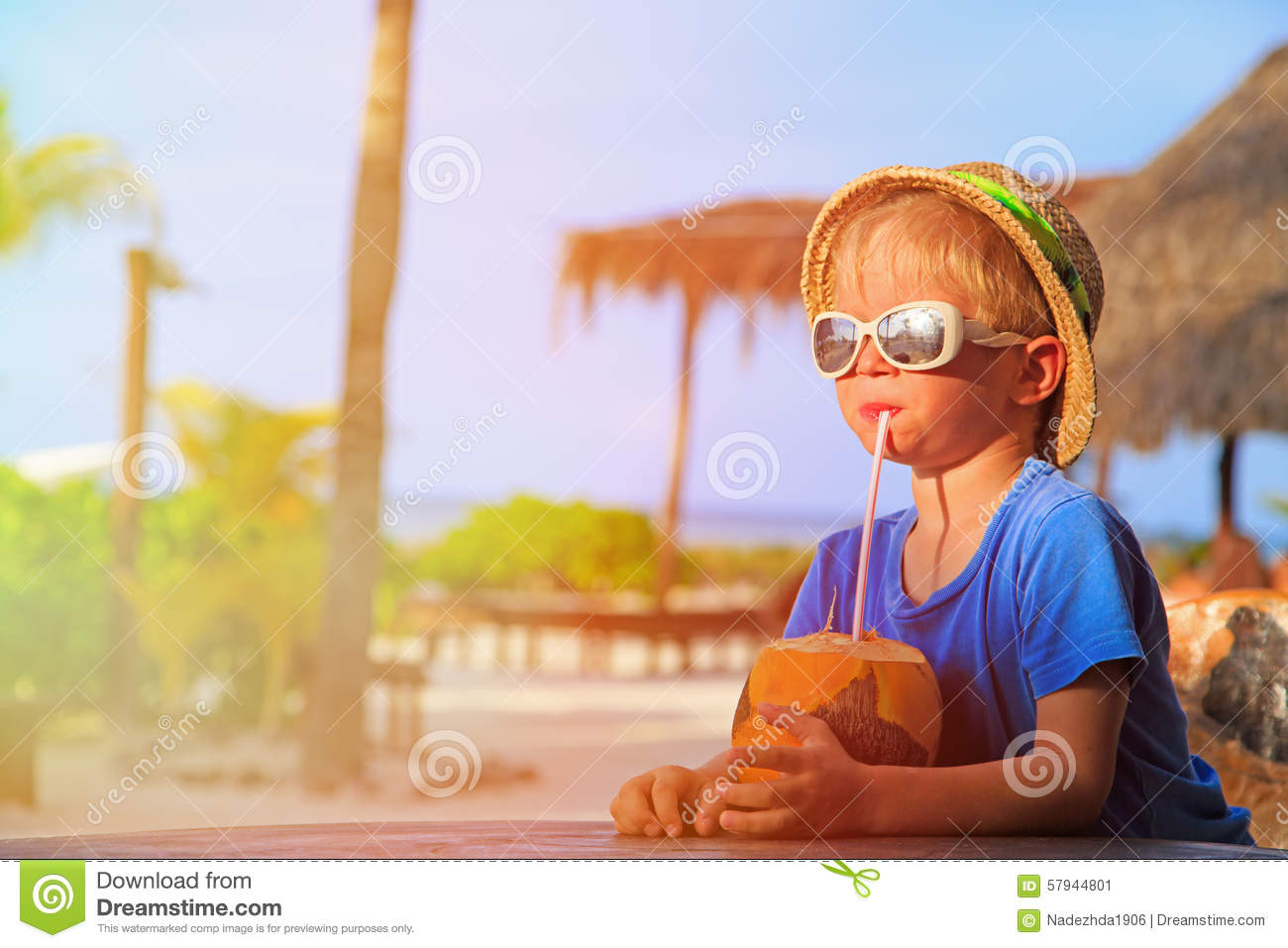 Little boy drinking coconut cocktail on beach