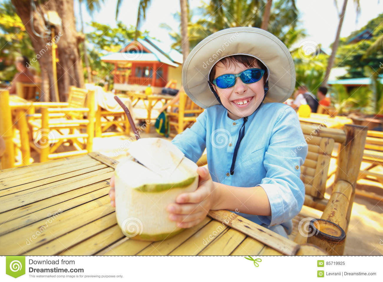 Little boy drinking coconut cocktail on tropical beach resort
