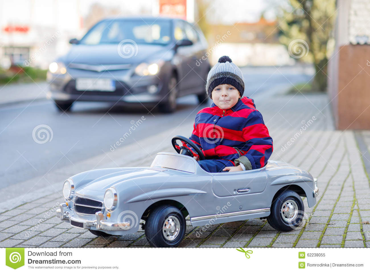 little boy driving big toy car and having fun outdoors stock photo