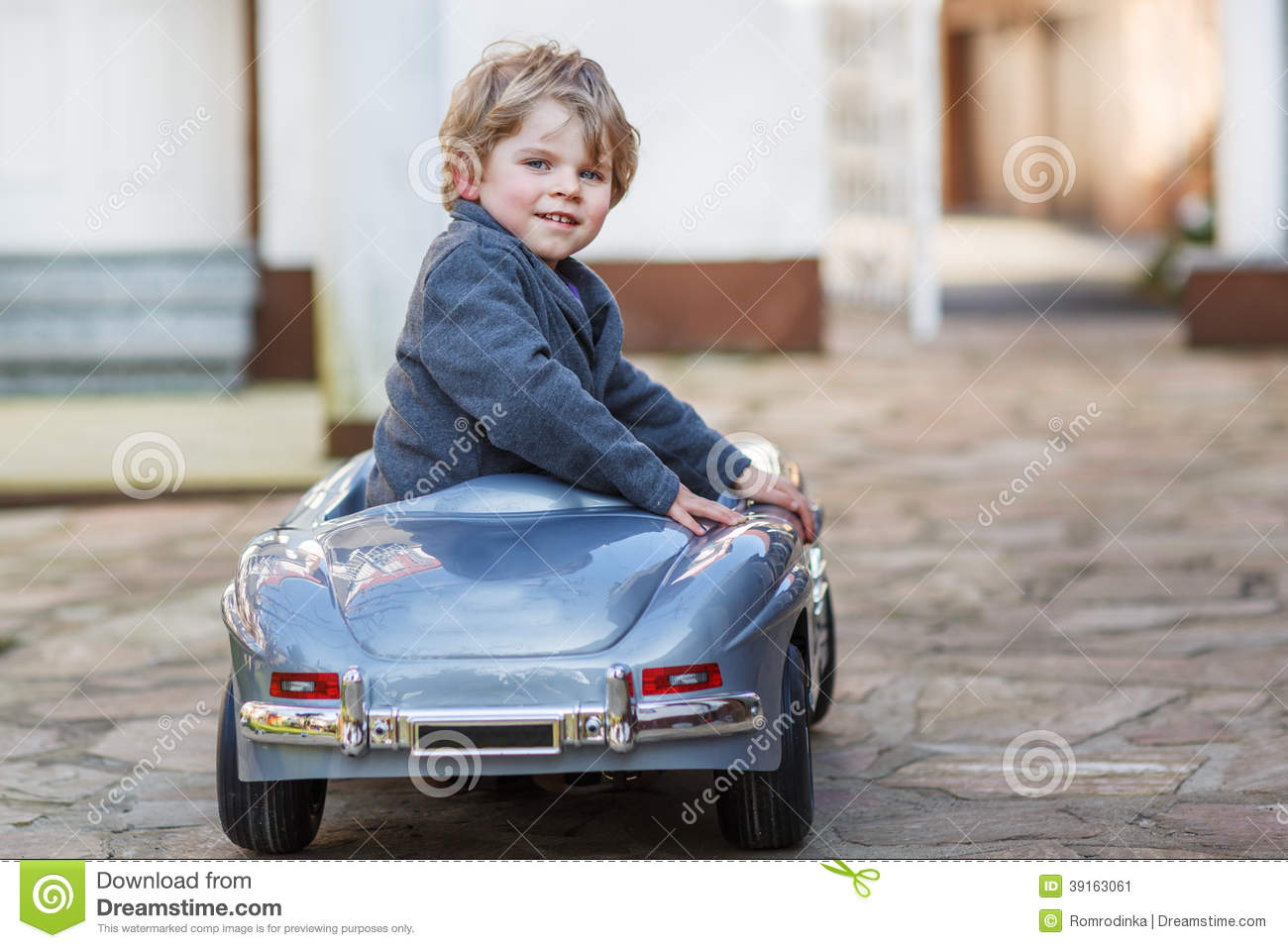 Little Big Boys Toys : Little boy driving big toy car outdoors stock image