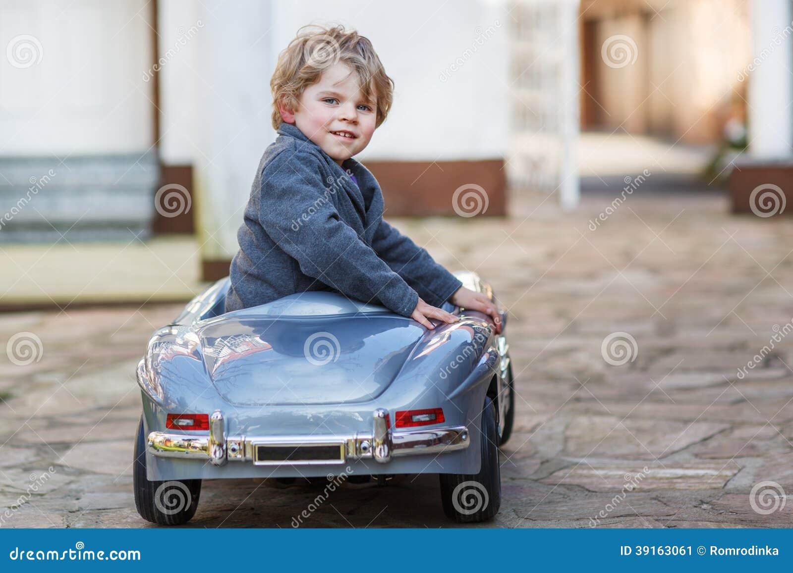 Little Big Boys Toys : Little boy driving big toy car outdoors
