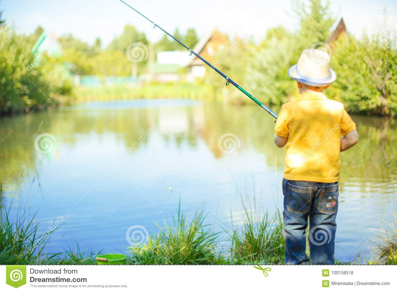 Little boy is engaged in fishing in a pond. Child with a dairy i