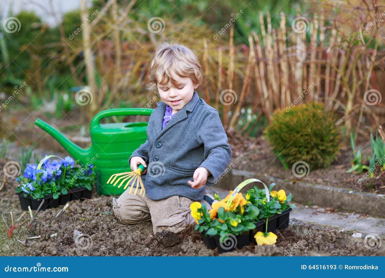 Boy gardening planting flowers blond years having fun vegetable plants