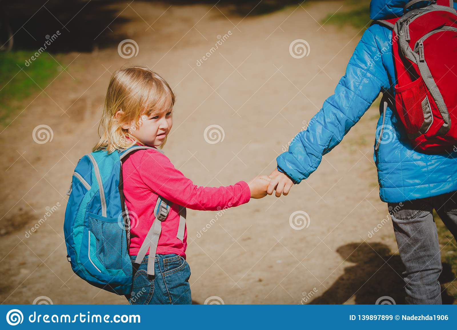 Little boy and girl with backpacks going to school