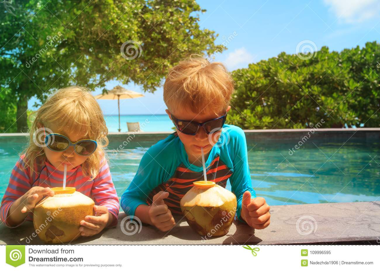 Little boy and girl drinking coconut cocktail on beach resort