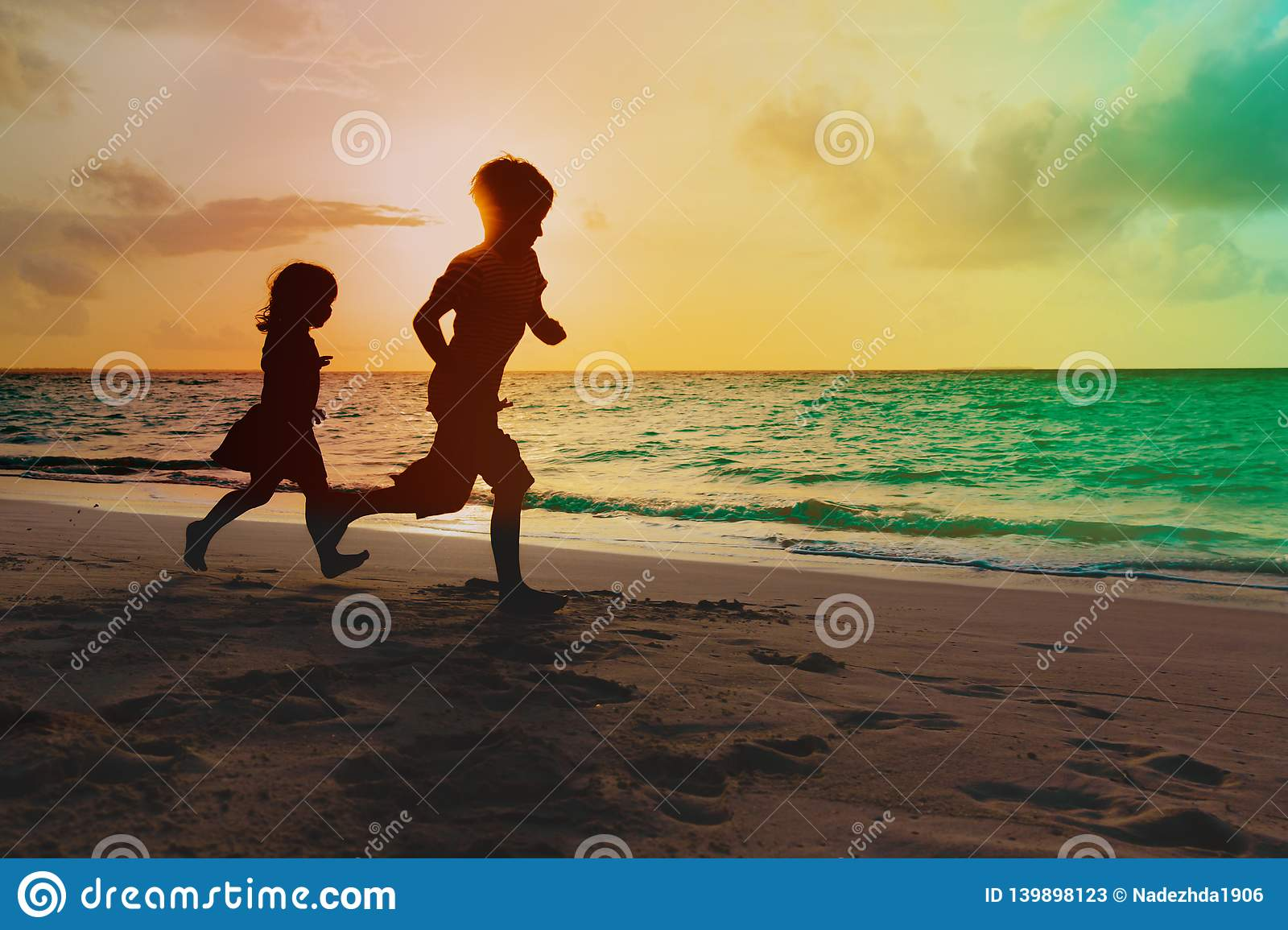 Little boy and girl run play at sunset tropical beach