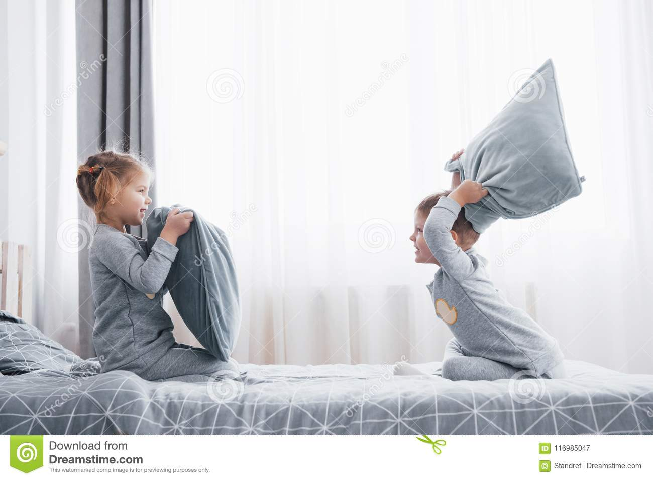 Little boy and girl staged a pillow fight on the bed in the bedroom. Naughty children beat each other pillows. They like