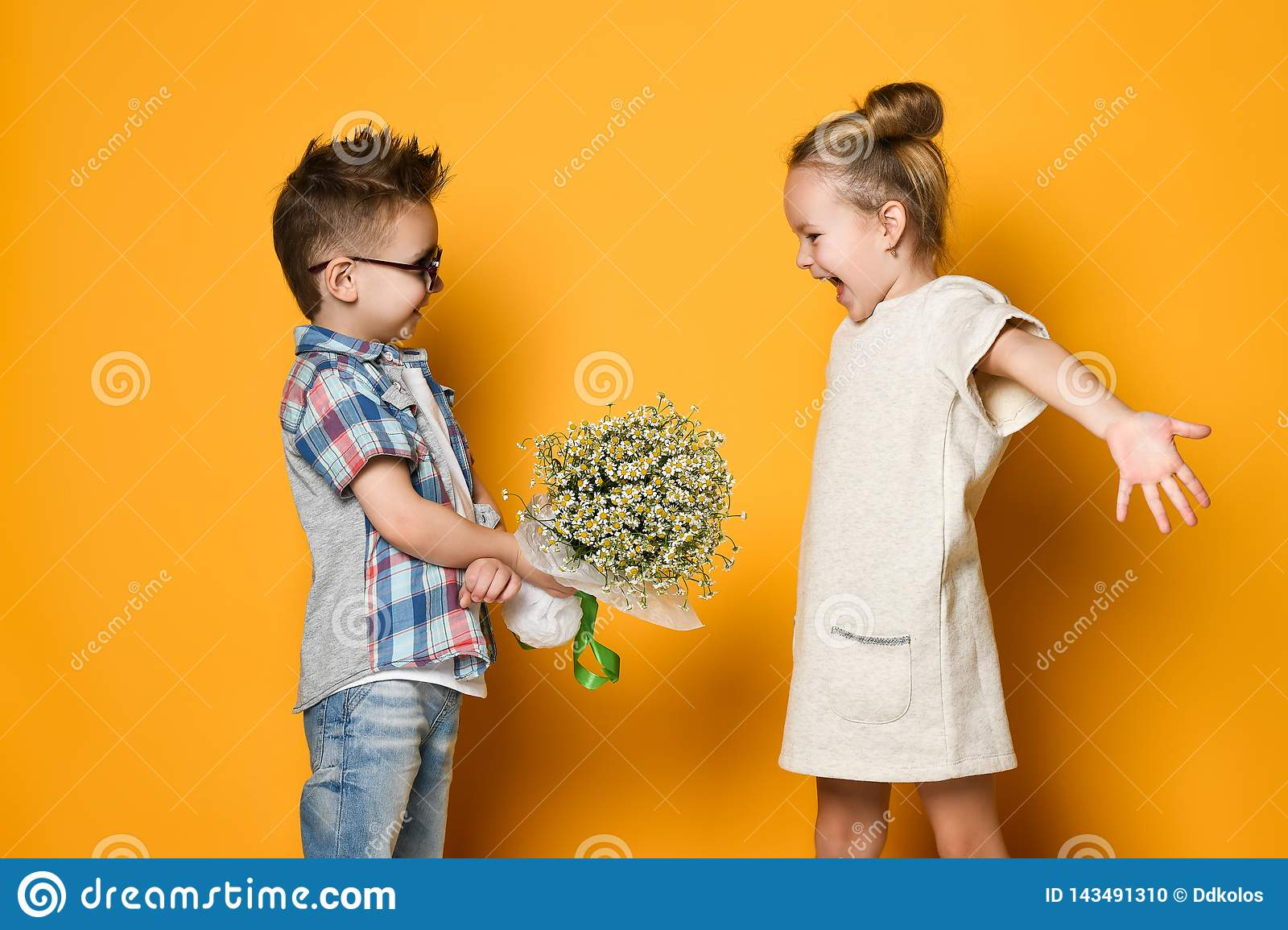 Happy caucasian people boy gives a flowers to his girlfriend isolated over yellow background.