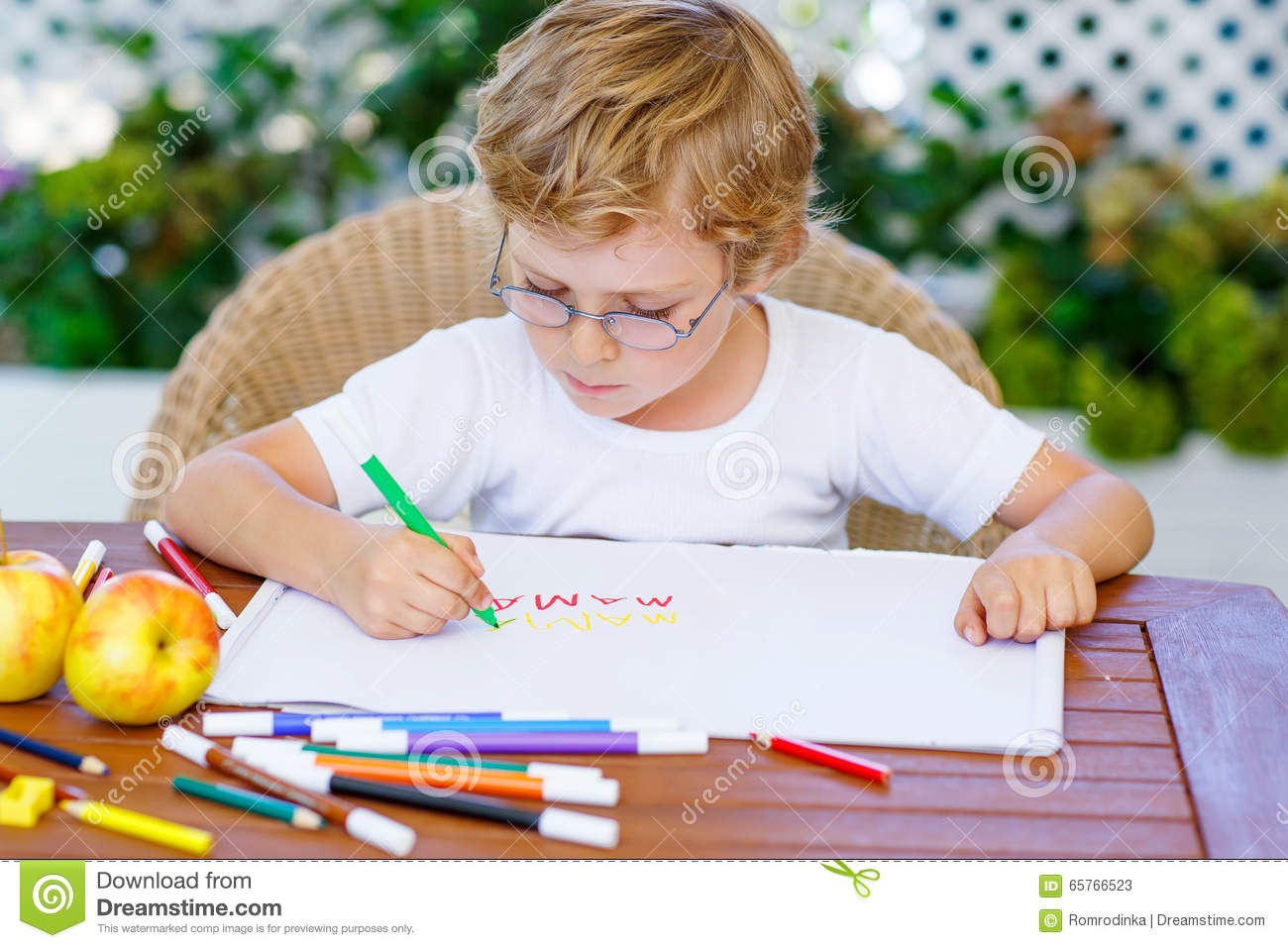 a4de8067a21 Portrait of cute happy preschool kid boy with glasses at home making  homework. Little child painting with colorful pencils
