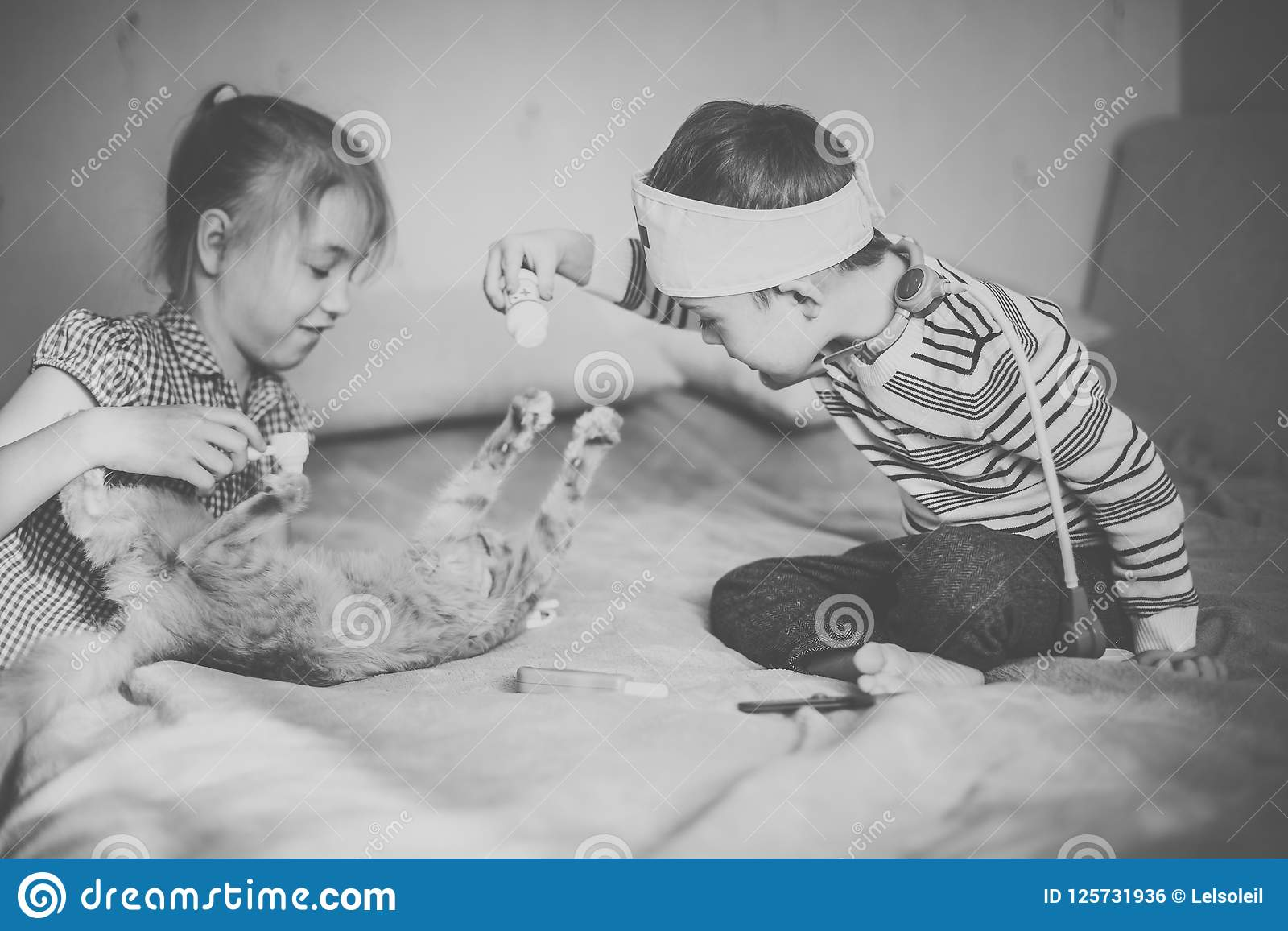 Little boy in the glasses with syndrome dawn and blonde girl play with toys and ginger cat. Black and white
