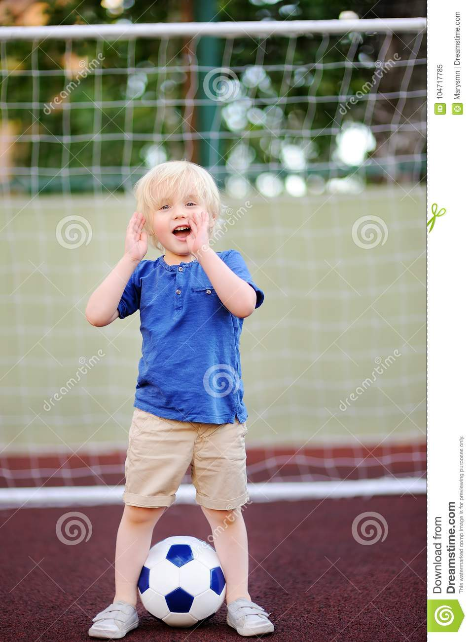 Little boy having fun playing a soccer/football game on summer day