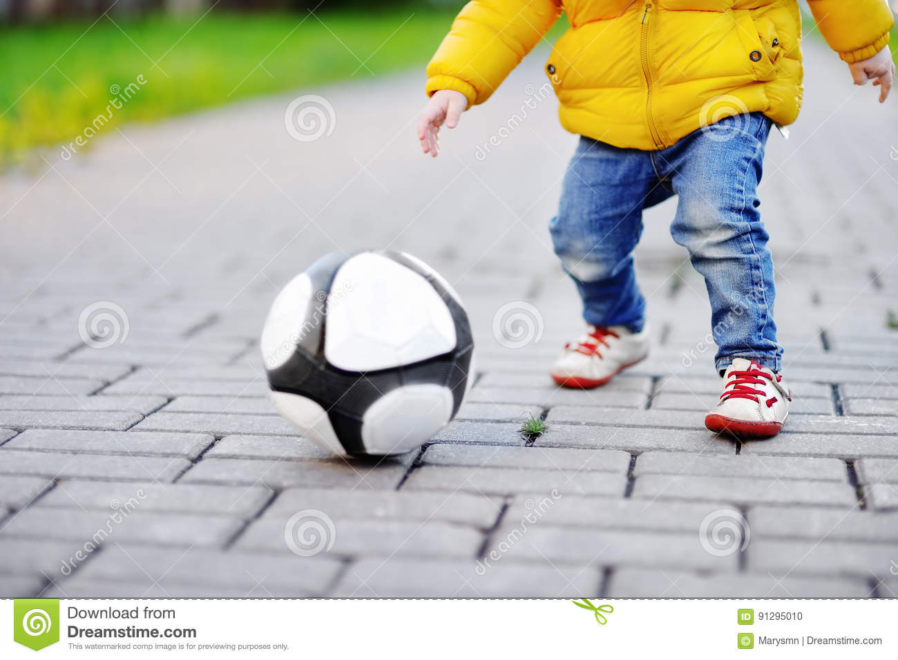 Little boy having fun playing a soccer game on sunny spring or autumn day
