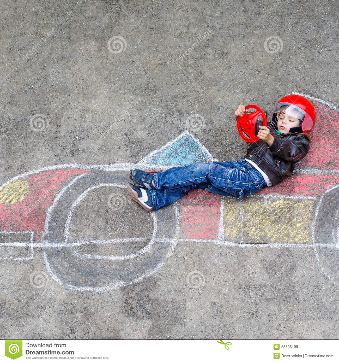 little boy having fun with race car drawing with chalks stock